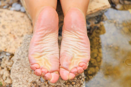wet female soles, feet on the lake in summer