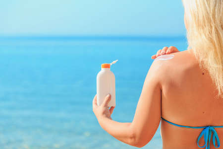Woman holding Suntan Lotion and applying it at The Beach, skin sun protection