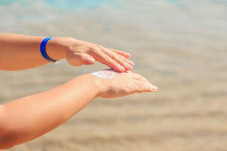 Le mani delle donne applicano una lozione solare sulla pelle, proteggono dal sole.