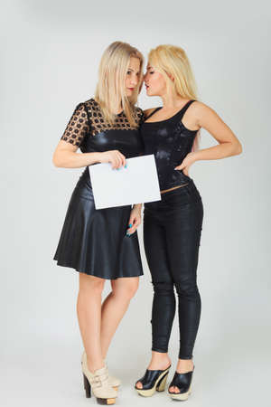 gossips elegant young women in black holding blank sign with copy space for text