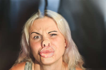 female face pressed against glass or window,  funny female face expression Imagens