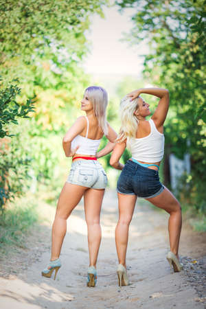 Modern youth female fashion trends, two girls in outfits with visible thongs