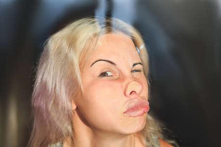 rostro femenino presionado contra el vidrio o la ventana, expresión divertida del rostro femenino Foto de archivo