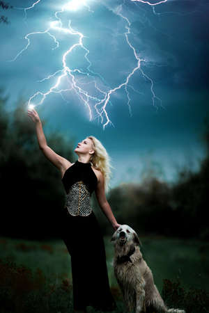 beautiful witch girl controls lightning strike with her angry dog, Halloween