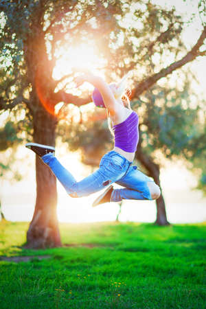 young teen girl in ripped jeans dances and jumps in the Park Reklamní fotografie