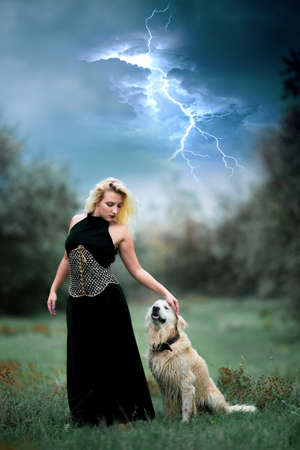young pretty woman in long black dress and her dog golden retriever on background of sky with lightning strike
