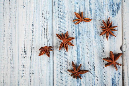 dried star anise flowers on light wooden table with copyspace on left
