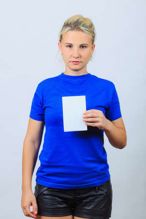 Young blonde girl in dark blue shirt and leather shorts holds blank brochure, booklet, pamphlet, leaflet with copyspace