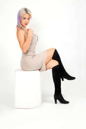 Mädchenmodell im kurzen beigefarbenen Kleid und schwarzen Stiefeln, die auf einem weißen Würfel sitzen Standard-Bild