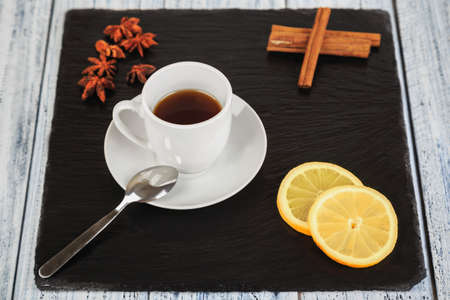 white cup of hot tea, cinnamon sticks, star anise and lemon slices on black slate square stone