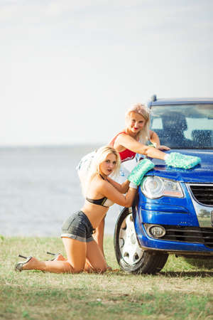 two sexy girls in bikini washes the car in mittens for car washing