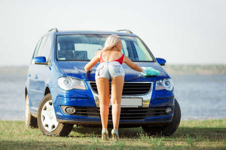 back view of sexy blonde girl washes the car hood with mittens 版權商用圖片