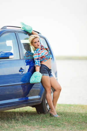 young sexy girl in mittens for car washing poses  near blue car