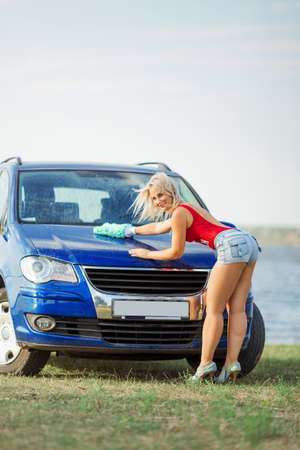 back view of sexy blonde woman washes the car hood with mittens