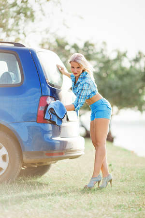 young sexy woman washes the car, hot girl  wash rear car headlight with blue towel