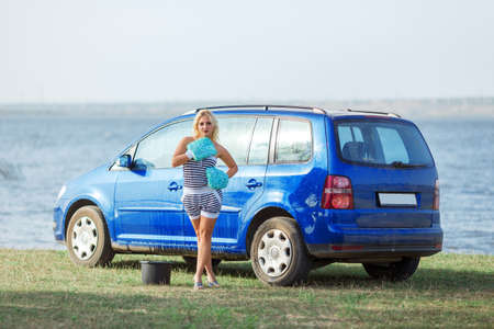 young sexy blonde woman in  car washing mittens on background of blue car