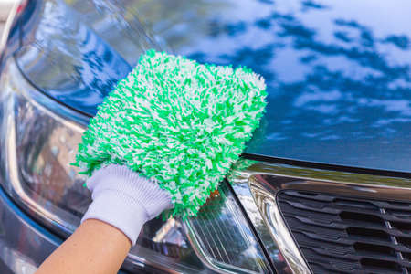 car cleaning with green fluffy washing mitten close up