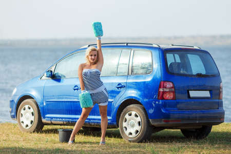 front view of young sexy blonde woman in  car washing mittens on background of blue car