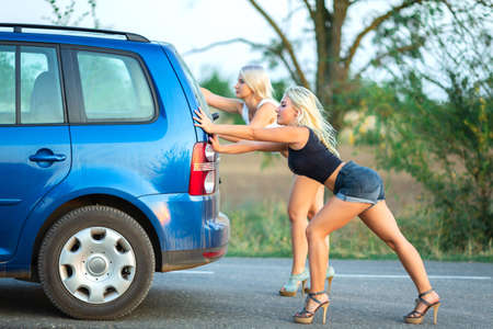 two hot blonde women  on high heels pushing broken car on roadside Stockfoto