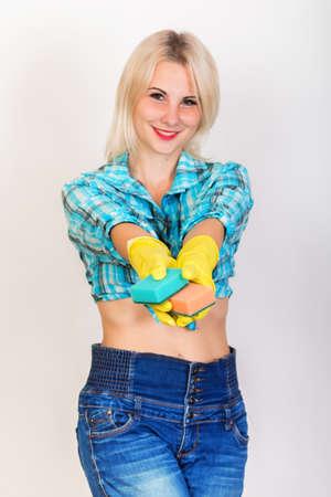 Feliz sonriente mujer rubia ama de llaves con guantes de goma amarillos mirando a la cámara y muestra esponjas para lavar