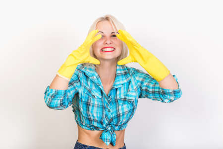 Funny blonde woman housekeeper wearing yellow rubber gloves demonstrate her teeth Imagens