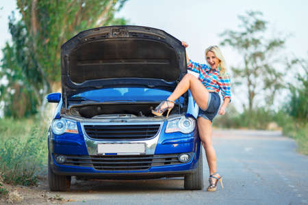 young beautiful woman poses near blue car with opened hood on road