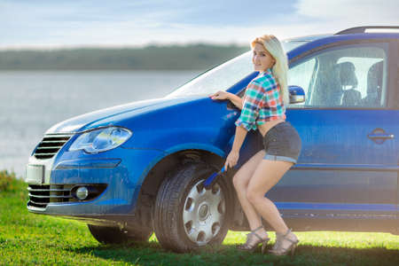 smiling hot young girl washes the car with wheels brush in sunny day