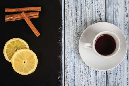 cup of hot coffe on rustic table and cinnamon sticks and lemon on black chalkboard, flat lay, top view