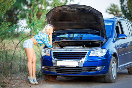 beautiful girl repairs car on the road, sexy hot woman mechanic looks under car hood Stock Photo