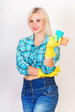 Happy smiling blonde woman housekeeper wearing yellow rubber gloves looking at camera and demonstrate sponges for washing Archivio Fotografico