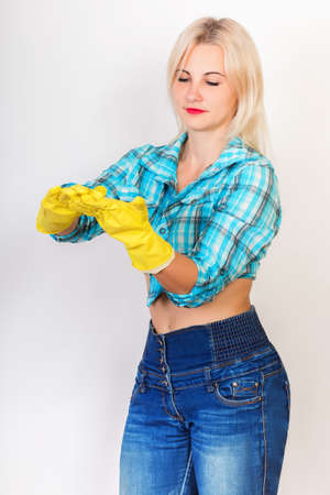 Blonde woman housekeeper wearing yellow rubber gloves cleaning something on her hands Archivio Fotografico