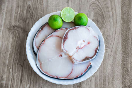 raw blue shark meat and lime on white plate