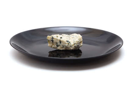 Piece of blue cheese with mold on black plate Stock fotó