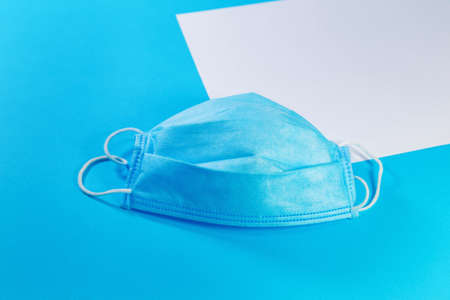 white sheet of paper and medical mask on blue background with copy space. Medical background, top view Stockfoto