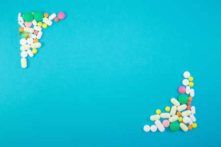 Group of colorful pills in left upper corner and right lower corner on blue background