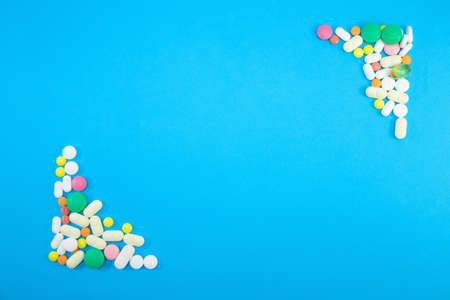 Group of colorful pills in left lower corner and right upper corner on blue background