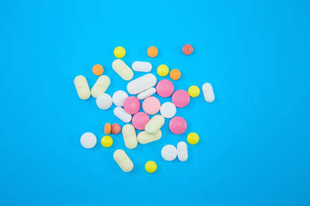 Heap of colorful pills on blue background