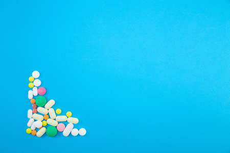 Group of colorful pills in left lower corner on blue background Stockfoto