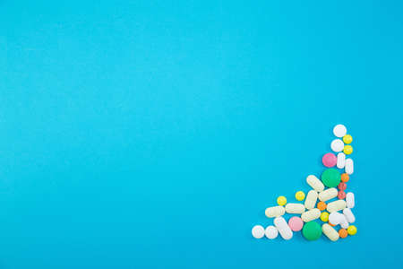 Group of colorful pills in right lower corner on blue background