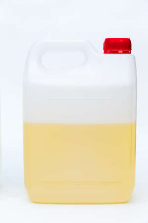 Plastic canister with yellow liquid on white background.