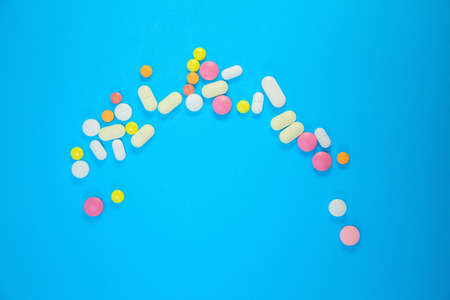 scattering of medical colorful pills on blue background