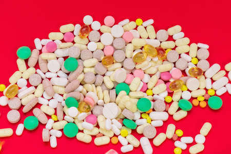 Colorful Medical pills on red background. Top view. Medicine concept