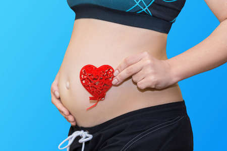 pregnancy, motherhood and maternity concept - happy future mother holding red heart on blue background Stockfoto