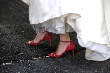 mariage: close up shot of a woman walking in a dress and red shoes