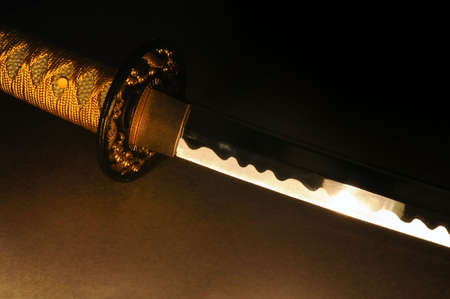 a close up shot of a samurai sword lit by candel light Stock Photo