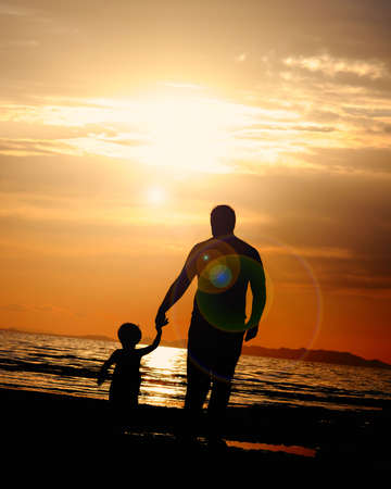 a father walking into the sunset with his son photo