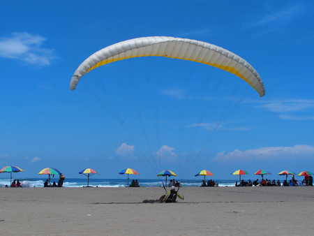 A man on a paraglide by the beach Stock Photo