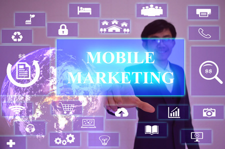advertise: MOBILE MARKETING  concept  presented by  businessman touching on  virtual  screen ,image element furnished by NASA Stock Photo