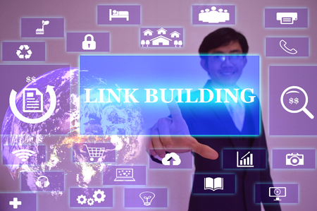 linkbuilding: LINK BUILDING concept  presented by  businessman touching on  virtual  screen ,image element furnished by NASA