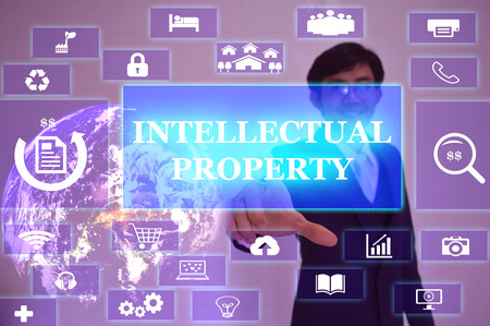 exclude: INTELLECTUAL PROPERTY concept  presented by  businessman touching on  virtual  screen Stock Photo